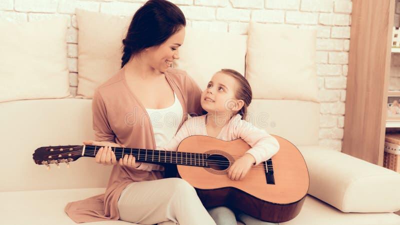 La mère enseigne la fille jouant la guitare à la maison images stock