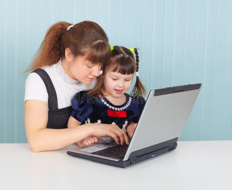 La mère enseigne l'enfant à utiliser l'ordinateur portatif photo stock