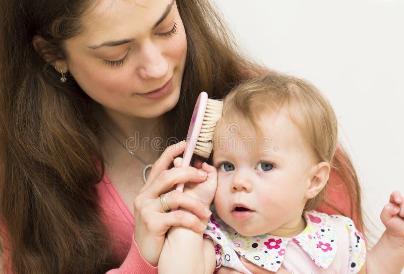 La mère enseigne la fille à balayer des cheveux. photo libre de droits