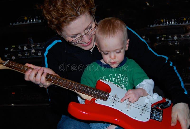 La mère enseigne la leçon de musique de guitare d'enfant photographie stock libre de droits