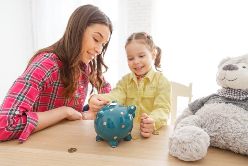 La mère enseigne sa fille à épargner l'argent photographie stock libre de droits