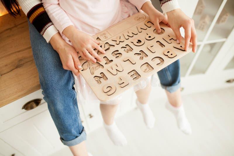 La mère enseigne sa fille à lire utilisant l'alphabet en bois des enfants images stock