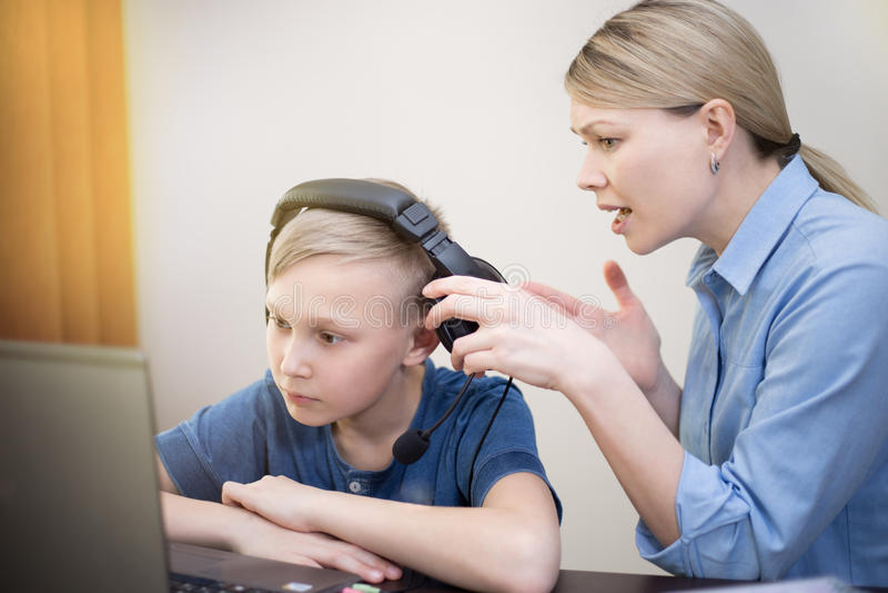 La mère essaye d'attirer l'attention du fils travaillant avec le carnet avec des écouteurs images stock