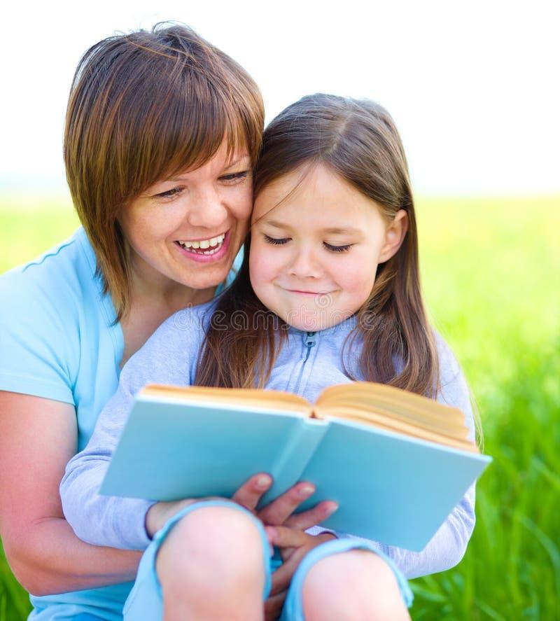 La mère est livre de lecture avec sa fille photo libre de droits