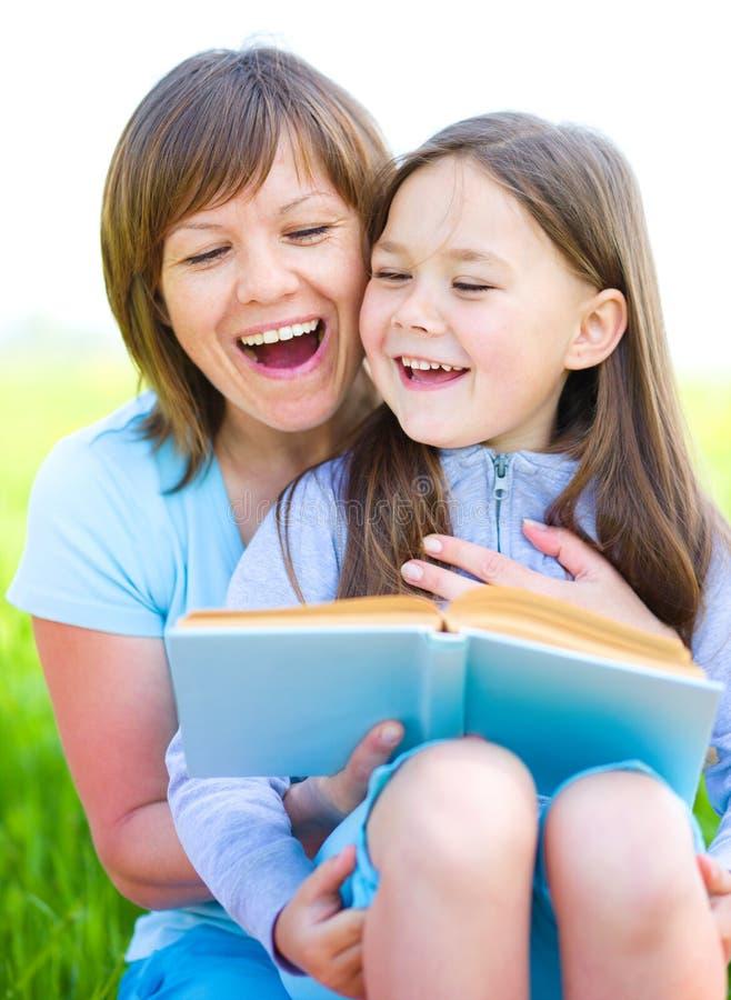 La mère est livre de lecture avec sa fille images libres de droits