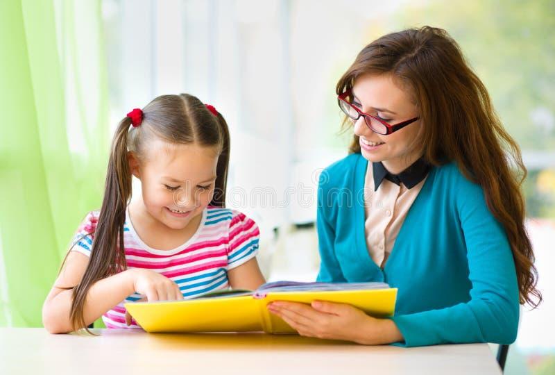 La mère est livre de lecture avec sa fille photographie stock libre de droits