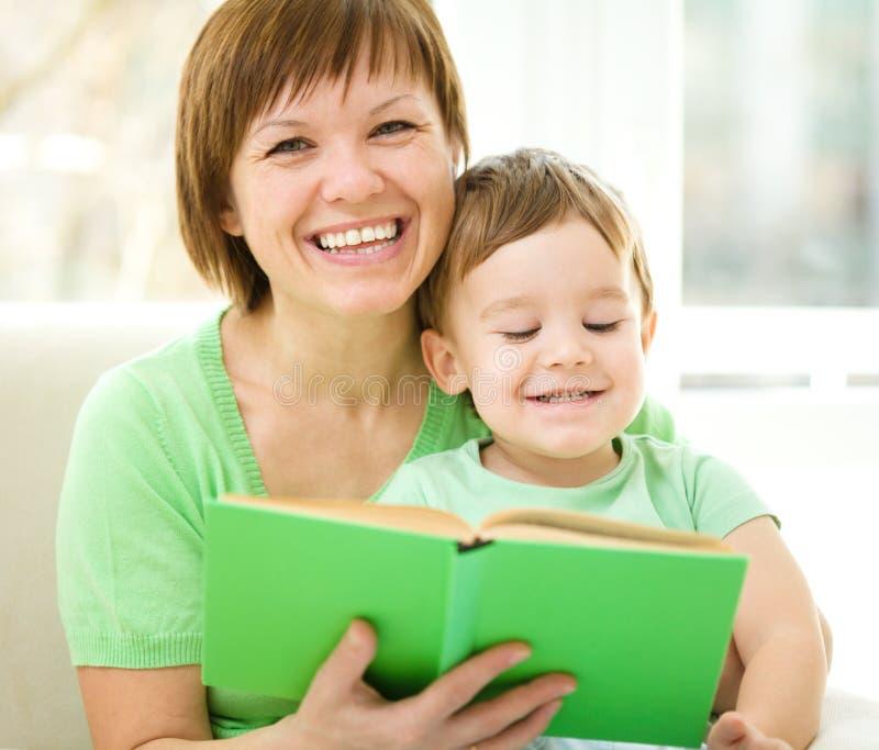 La mère est livre de lecture pour son fils images stock