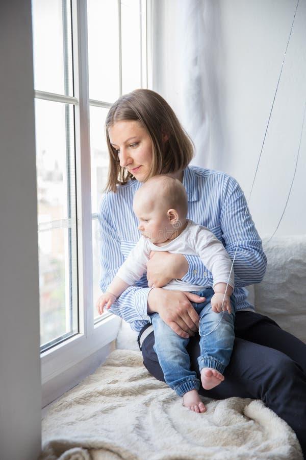 La mère est tenante et étreignante sa fille de bébé photo stock