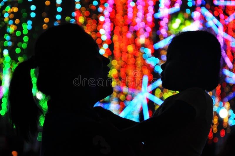 La mère et la fille apprécie l'affichage coloré de lumières de Noël dans la ville de Makati, Philippines photo stock