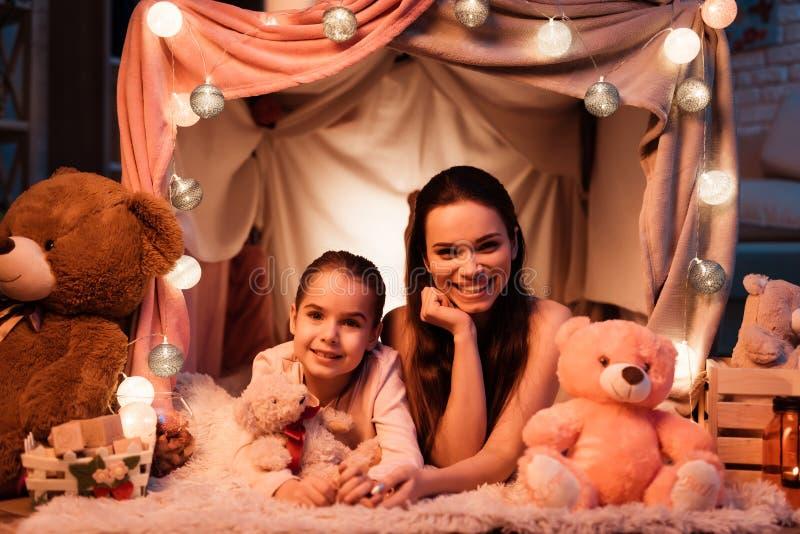 La mère et la fille avec des ours de nounours dans l'oreiller logent tard la nuit à la maison images libres de droits