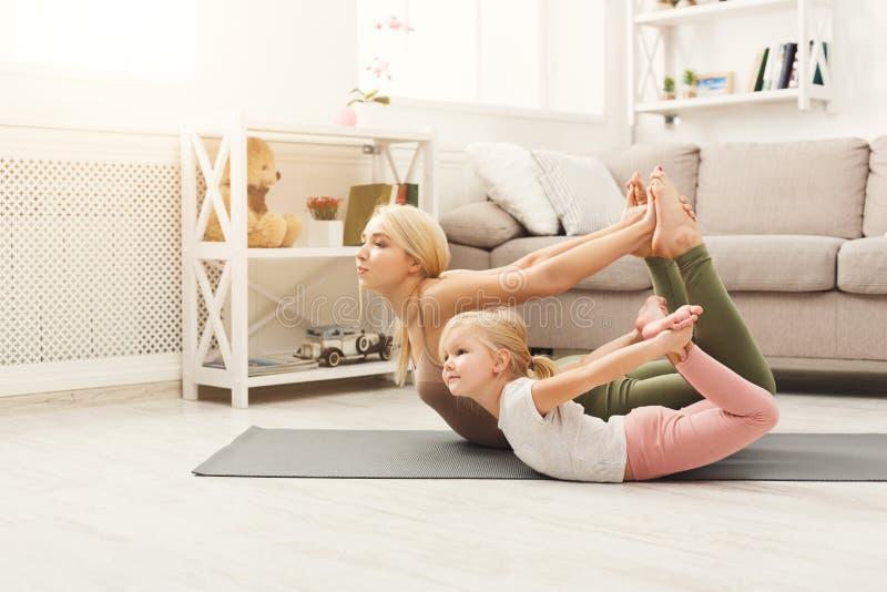La mère et la fille faisant le yoga s'exerce à la maison photo stock