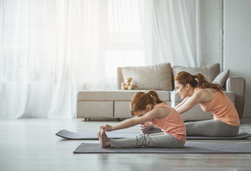 La mère et la fille font étirant des exercices à la maison photo libre de droits