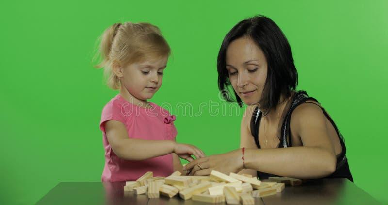 La mère et la fille joue le jenga Enfant faisant une tour à partir des blocs en bois photographie stock libre de droits