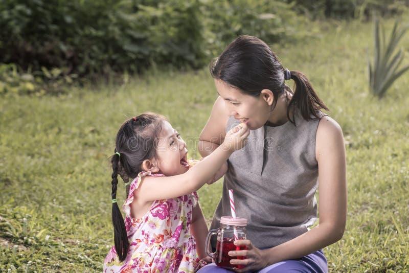 La mère et la fille mangent heureusement des biscuits images libres de droits