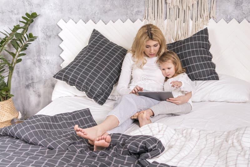 La mère et la fille tiennent un comprimé photographie stock libre de droits