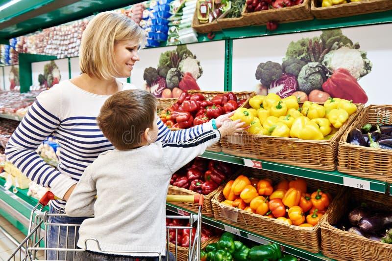 La mère et l'enfant avec le paprika dans les légumes font des emplettes photo stock