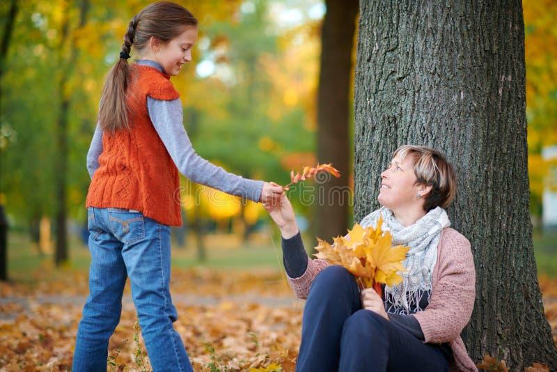 La mère et l'enfant sont en parc de ville d'automne Ils sont posants, souriants, jouants et ayants l'amusement Arbres jaunes lumi photos stock