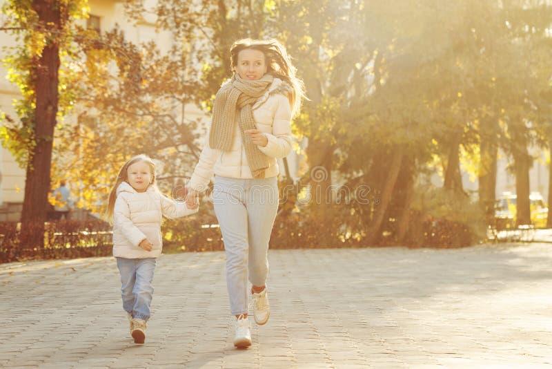 La mère et la fille courant par l'automne se garent images stock