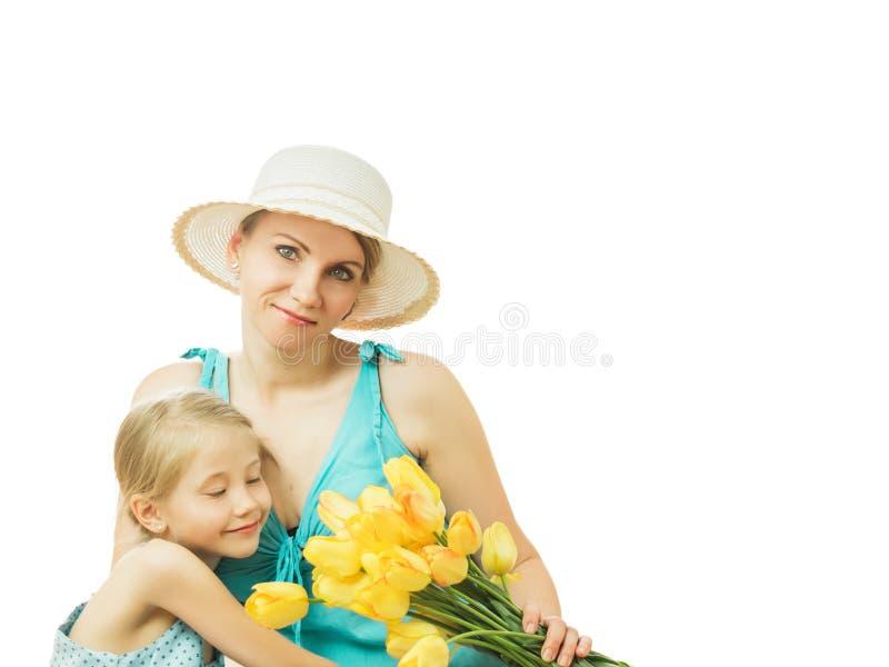 La mère et la fille et un bouquet des tulipes jaunes d'isolement sur le fond blanc image stock