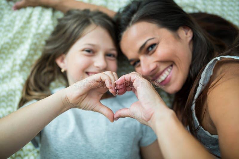 La mère et la fille faisant le coeur forment de la main tout en se trouvant sur le lit photographie stock