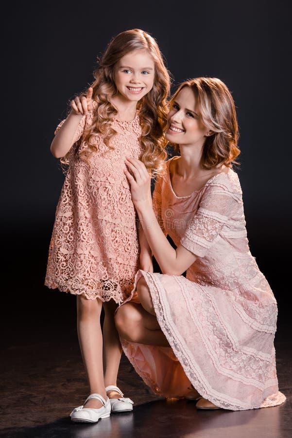 La mère et la fille heureuses dans le rose habille le pointage et le regard loin image libre de droits