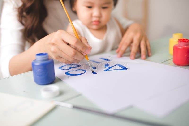 La mère et la fille heureuses de famille peignent ensemble Hel asiatiques de femme photographie stock