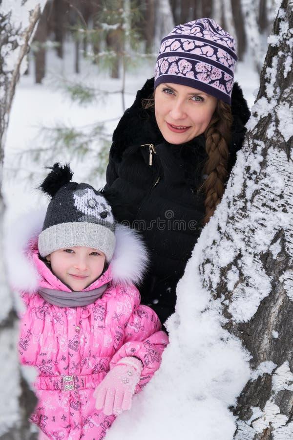 La mère et la fille marchent dans les bois d'hiver images stock
