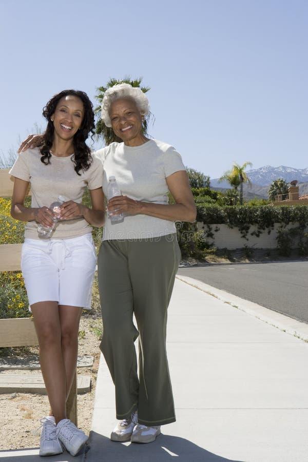 La mère et la fille se tient sur le trottoir dans les vêtements de sport image libre de droits