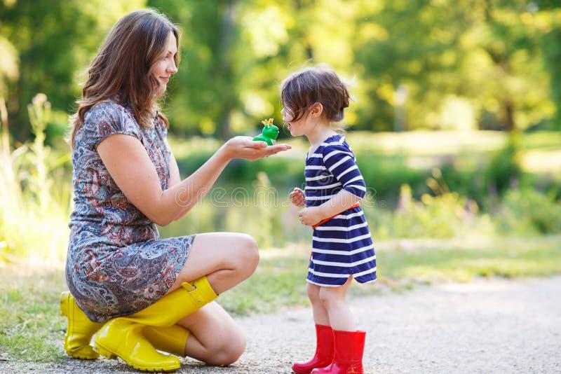 La mère et la petite fille adorable d'enfant en bas âge en caoutchouc jaune huent photo libre de droits
