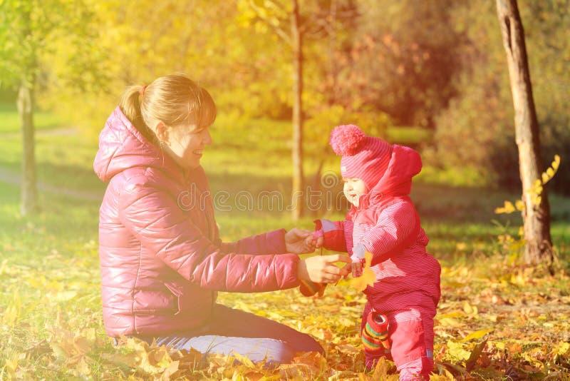 La mère et la petite fille mignonne jouent en automne images libres de droits