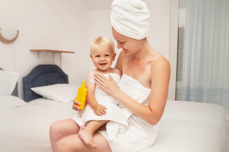 La mère et le bébé infantile heureux en serviettes blanches après s'être baigné appliquent la protection solaire ou après lotion  photographie stock libre de droits