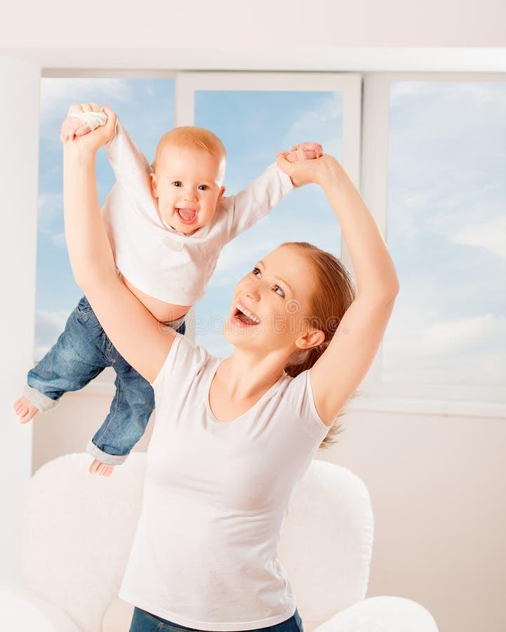 La mère et le bébé jouent les jeux actifs, font la gymnastique et le laug image stock