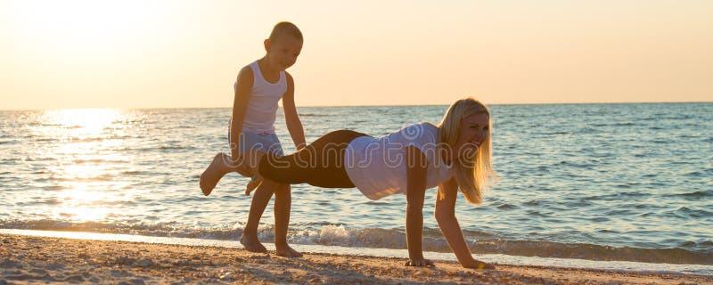 La mère et le fils font des exercices sur la plage, ils rencontrent le lever de soleil Forme physique, sport, yoga et concept sai images stock