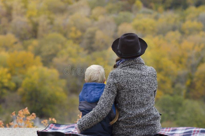 La mère et le fils s'asseyent sur une éminence Automne Forêt dans t photo libre de droits