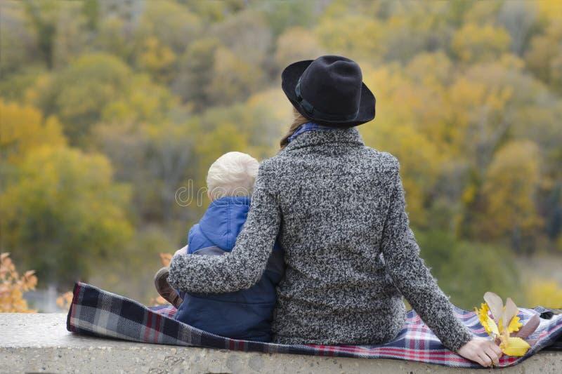 La mère et le fils s'asseyent sur une éminence Automne Forêt dans t image stock