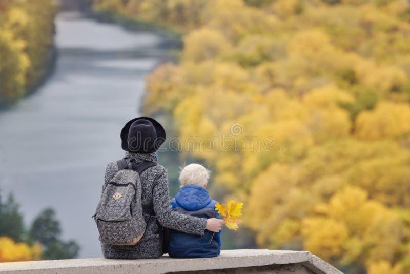 La mère et le fils s'asseyent sur une éminence Automne Rivière et forêt ci-dessous Vue arrière photo libre de droits