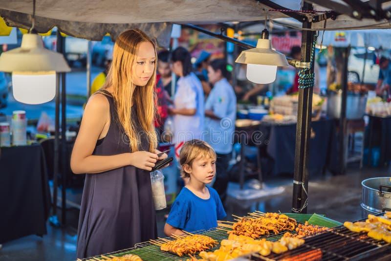 La mère et le fils sont des touristes sur le marché asiatique de marche de nourriture de rue images stock