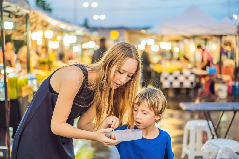 La mère et le fils sont des touristes sur le marché asiatique de marche de nourriture de rue photos libres de droits