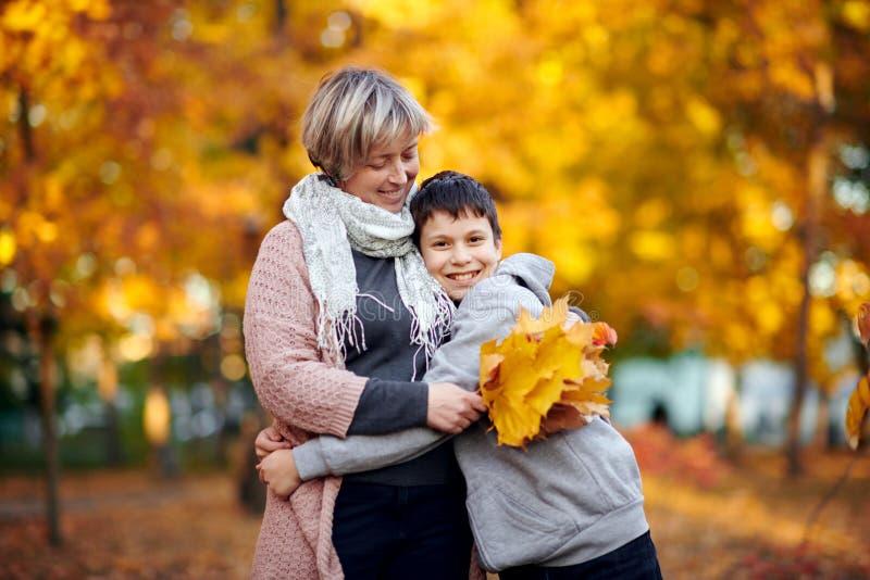 La mère et le fils sont en parc de ville d'automne Ils sont des parents posant, souriant, jouant et ayant l'amusement Arbres jaun photo libre de droits