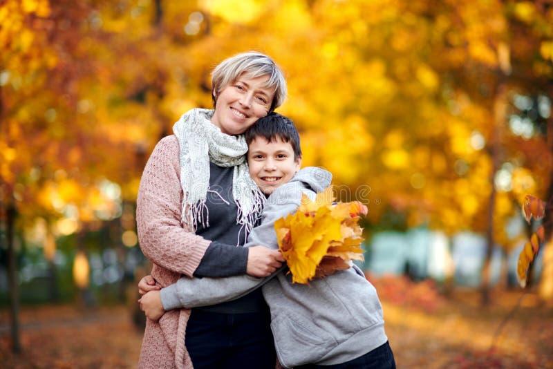 La mère et le fils sont en parc de ville d'automne Ils sont des parents posant, souriant, jouant et ayant l'amusement Arbres jaun images stock