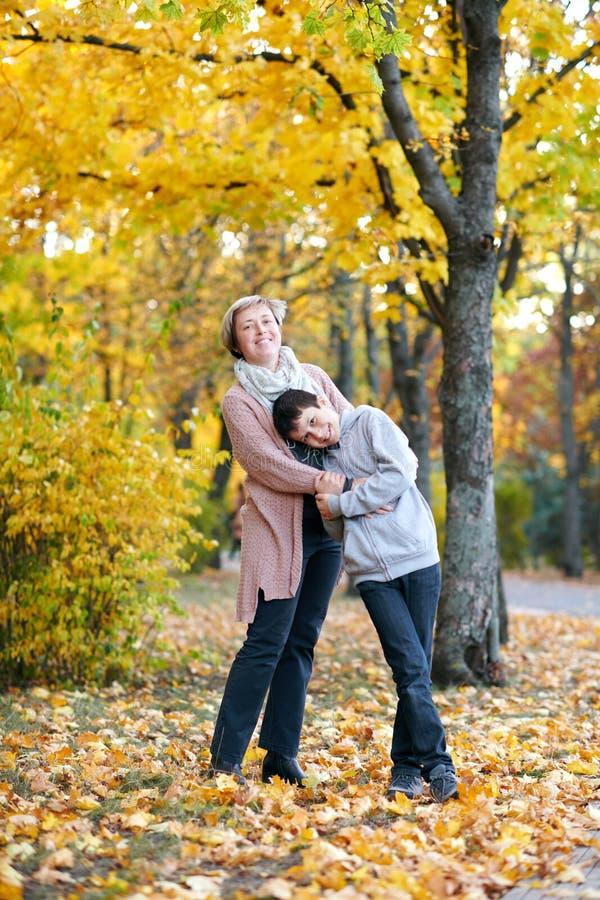 La mère et le fils sont en parc de ville d'automne Ils sont des parents posant, souriant, jouant et ayant l'amusement Arbres jaun image libre de droits