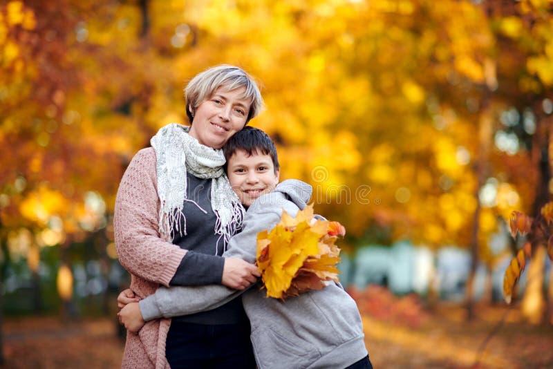 La mère et le fils sont en parc de ville d'automne Ils sont des parents posant, souriant, jouant et ayant l'amusement Arbres jaun photo stock