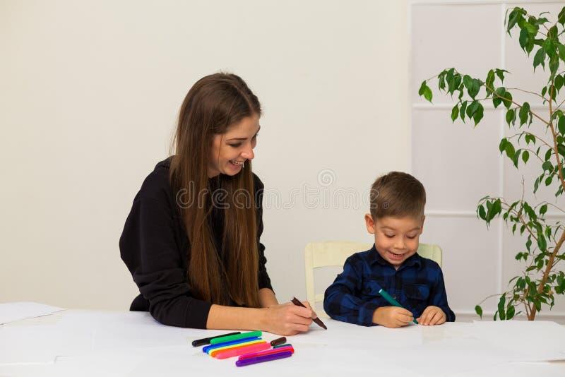 La mère et le jeune fils dessine une image à la table photo libre de droits