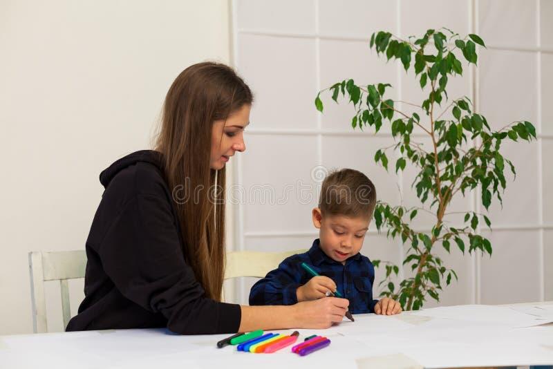 La mère et le jeune fils dessine une image à la table images libres de droits
