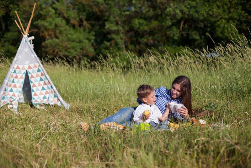 La mère et le jeune fils mangent au voyage de nature de pique-nique photos stock