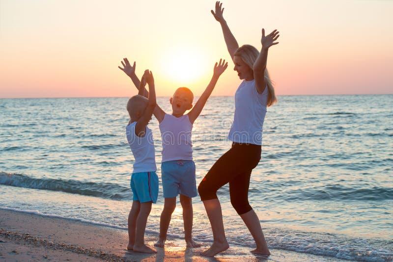La mère et les enfants font des exercices sur la plage, ils rencontrent le lever de soleil Forme physique, sport, yoga et concept image stock