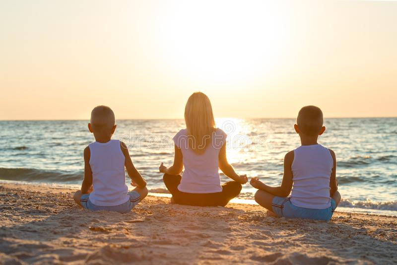 La mère et les enfants font des exercices sur la plage, ils rencontrent le lever de soleil Forme physique, sport, yoga et concept photo stock