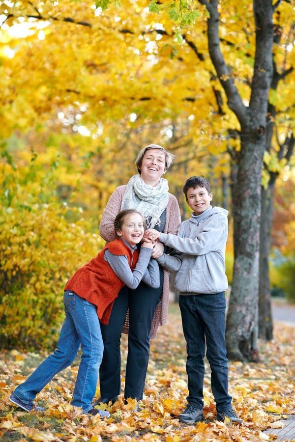 La mère et les enfants sont en parc de ville d'automne Ils sont des parents posant, souriant, jouant et ayant l'amusement Arbres  photographie stock libre de droits