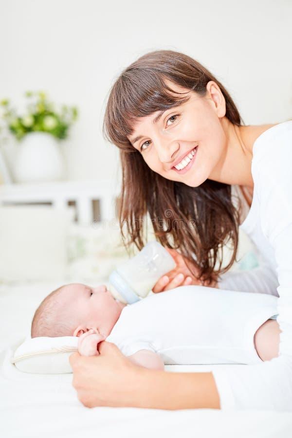 La mère heureuse alimente le bébé avec du lait photos libres de droits