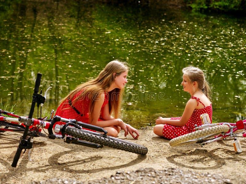 La mère heureuse avec la fille monte la bicyclette et se reposer sur la plage photographie stock